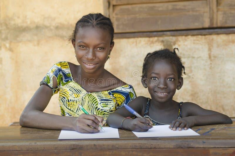 Scuola per i bambini africani - coppia sorridere mentre imparando il tog immagini stock libere da diritti