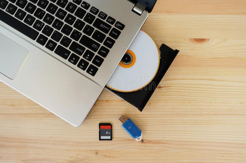 SD Card, Flash Drive USB3.0 and CD DVD Drive Writer Burner Reader of laptop computer on wooden background royalty free stock image