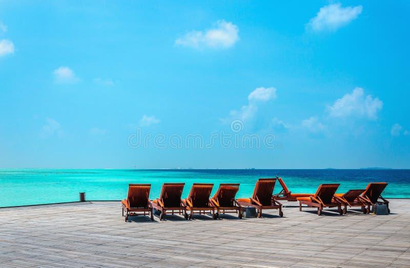 Sdrai arancio di legno su un pilastro sui precedenti dell'acqua azzurrata, Oceano Indiano, Maldive fotografie stock