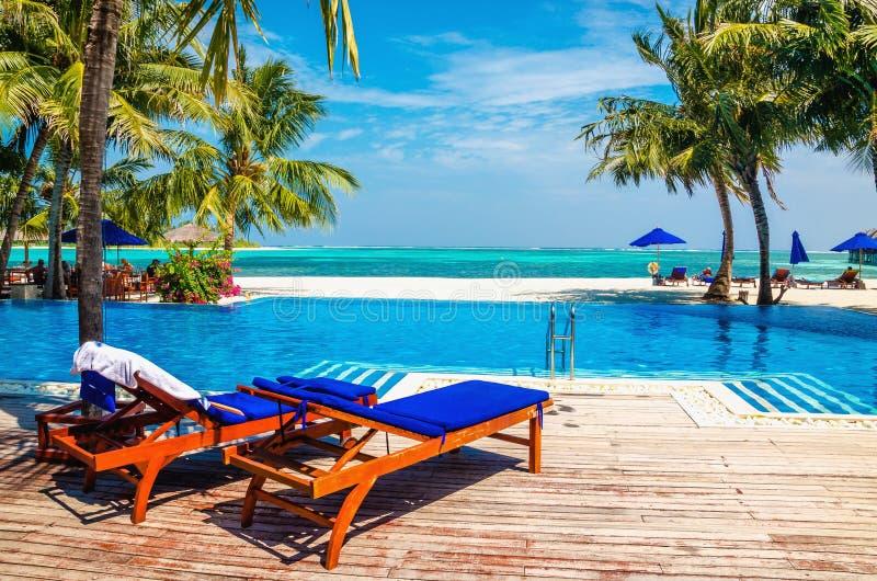 Sdrai di legno con i cuscini blu sopra lo stagno Nei precedenti, nell'acqua azzurrata dell'oceano ed in una spiaggia con immagini stock libere da diritti