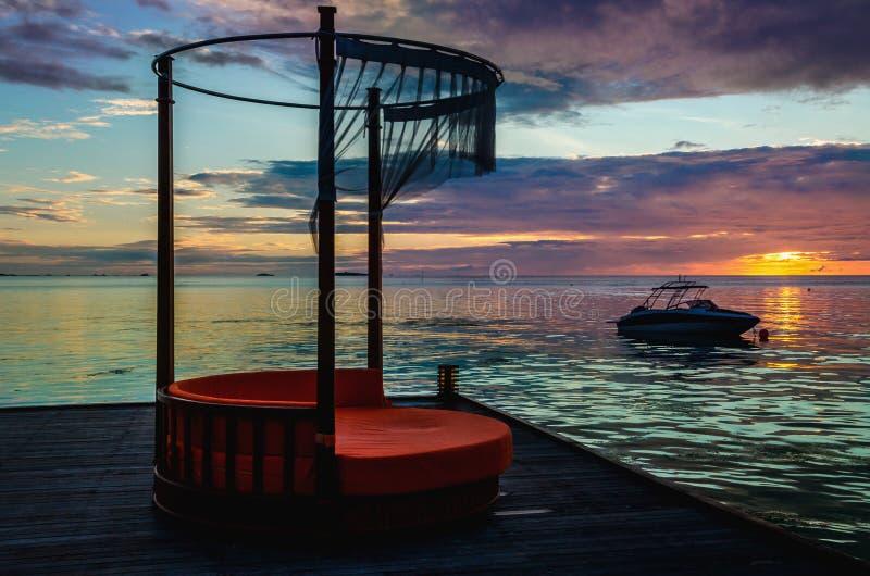 Sdraio lussuoso sui precedenti di bello tramonto variopinto sopra l'oceano, Maldive immagini stock