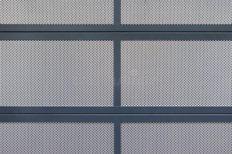 Seção de uma tampa feita de diversas placas da placa perfurada de prata, que são limitadas com perfis pintados azuis do metal fotos de stock royalty free