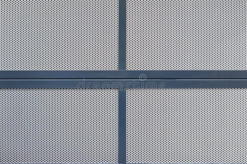 Seção de uma tampa feita de diversas placas da placa perfurada de prata, que são limitadas com perfis pintados azuis do metal fotografia de stock