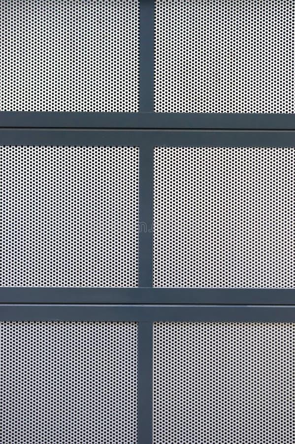 Seção de uma tampa feita de diversas placas da placa perfurada de prata, que são limitadas com perfis pintados azuis do metal foto de stock