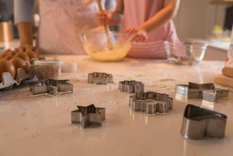 Seção meados de da mãe com sua filha que prepara o alimento na cozinha fotografia de stock