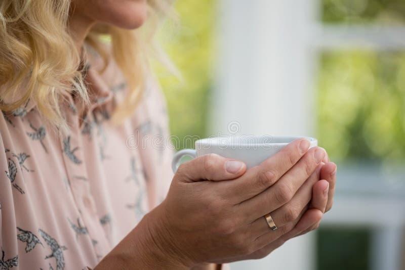 Seção meados de da mulher de negócios que guarda o copo de café foto de stock