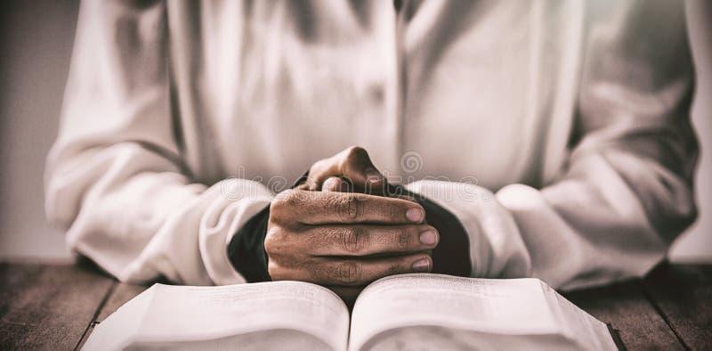 Seção meados de da mulher que senta-se na mesa pela Bíblia imagem de stock royalty free