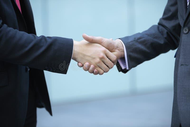 Seção meados de dos executivos que agitam as mãos foto de stock
