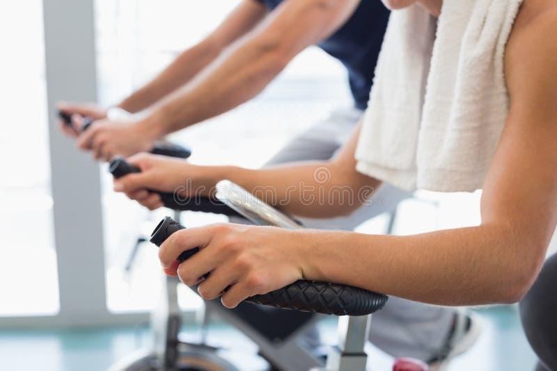Seção meados de dos pares do ajuste que trabalham em bicicletas de exercício no gym foto de stock royalty free