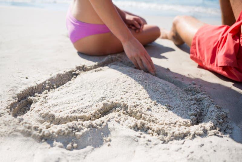 A seção meados de dos pares que sentam-se pela forma do coração cinzelou na areia na praia fotos de stock