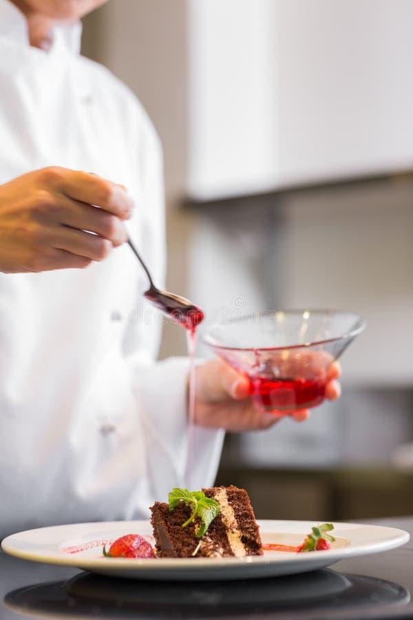 Seção meados de um cozinheiro chefe de pastelaria que decora a sobremesa na cozinha imagem de stock royalty free