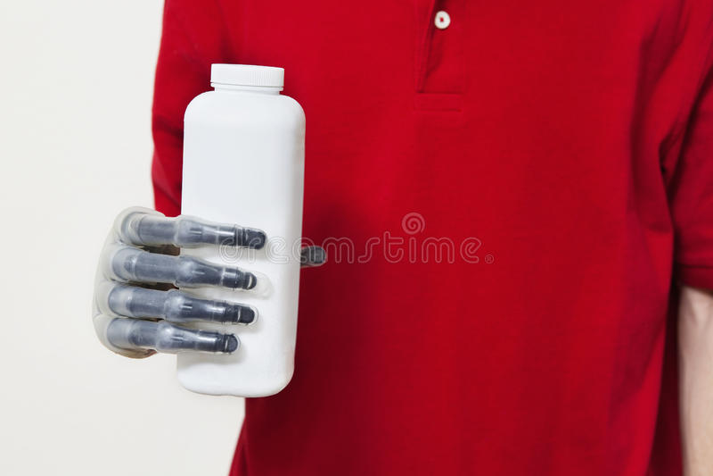 A seção meados de um homem que guarda a garrafa com protético cede o fundo cinzento fotos de stock