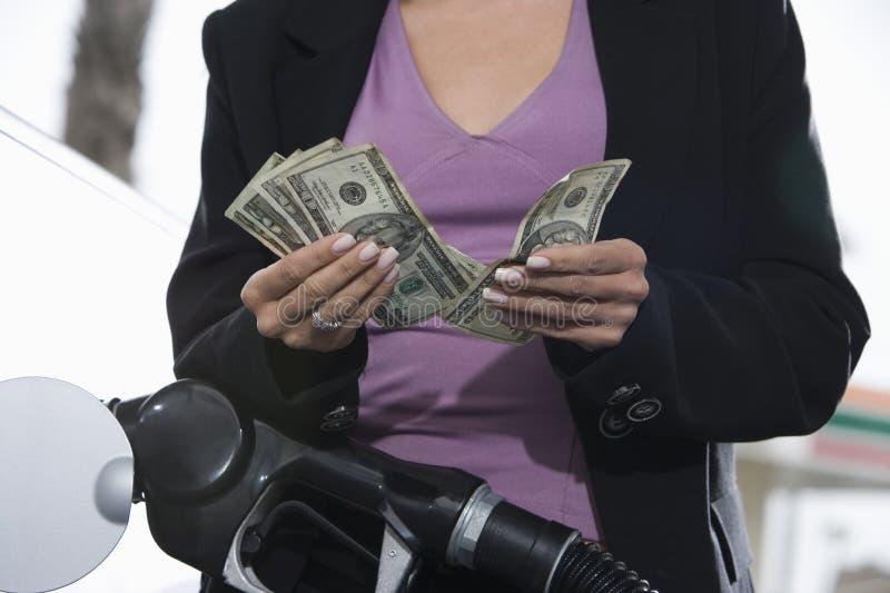 Seção meados de uma mulher que reabastece seu carro ao contar o dinheiro imagem de stock royalty free