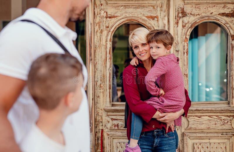 Seção mestra da família nova com as duas crianças pequenas que andam fora na cidade imagens de stock royalty free