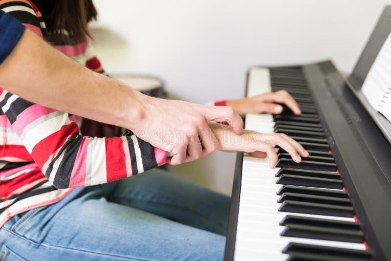 Seção mestra da menina que toma lições de piano do tutor fotografia de stock royalty free