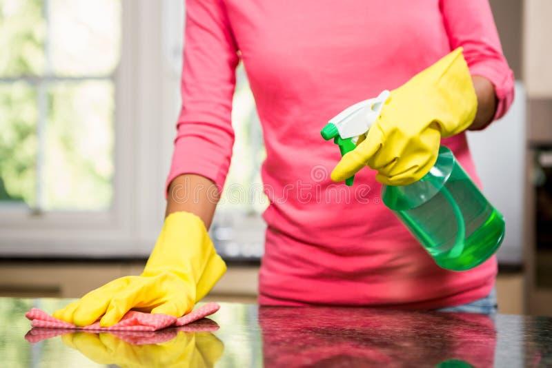 Seção mestra da mulher que limpa o contador imagens de stock