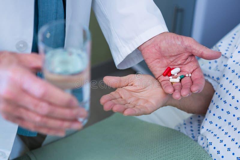 Seção mestra do doutor que dá o comprimido da medicina ao paciente imagens de stock