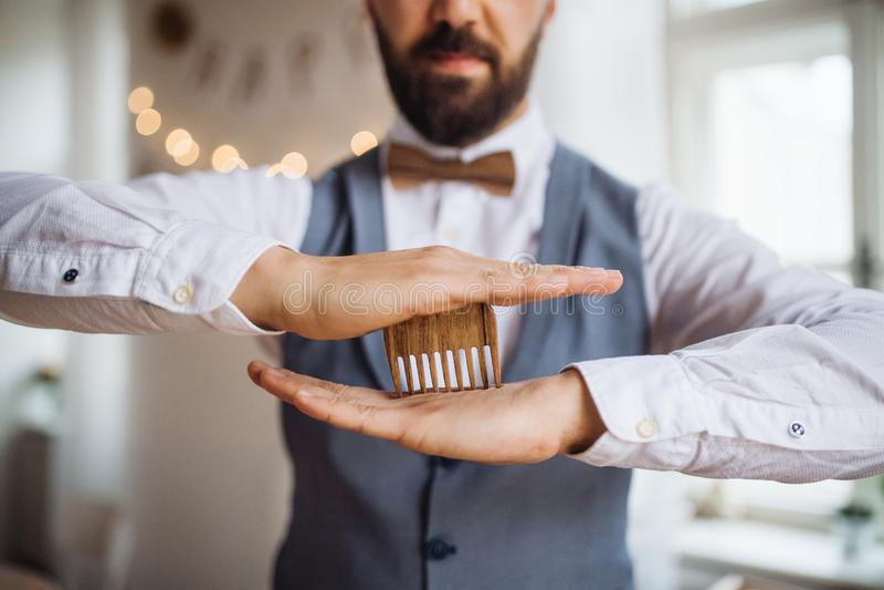 Seção mestra do homem que está dentro em um grupo da sala para um partido, guardando um pente da barba foto de stock