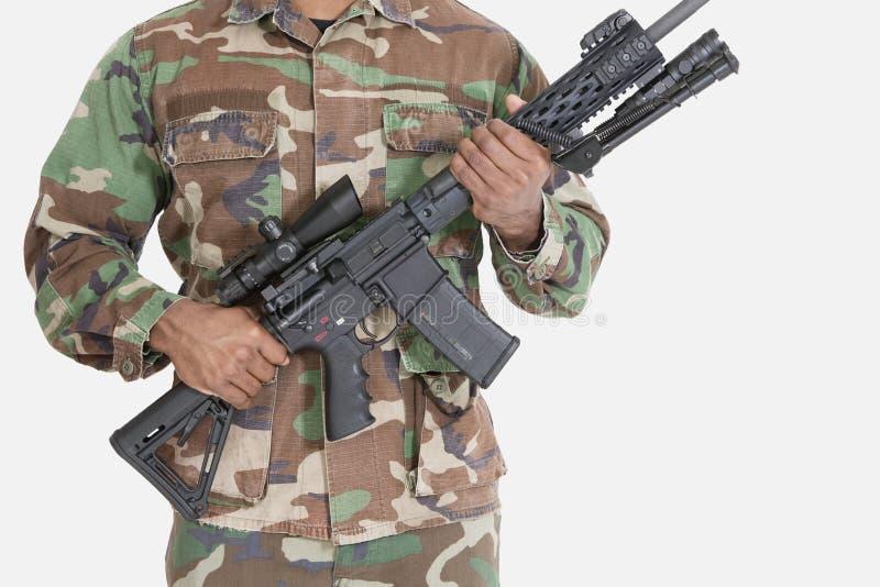 Seção mestra do soldado dos E.U. Marine Corps que guardara a espingarda de assalto M4 sobre o fundo cinzento fotografia de stock