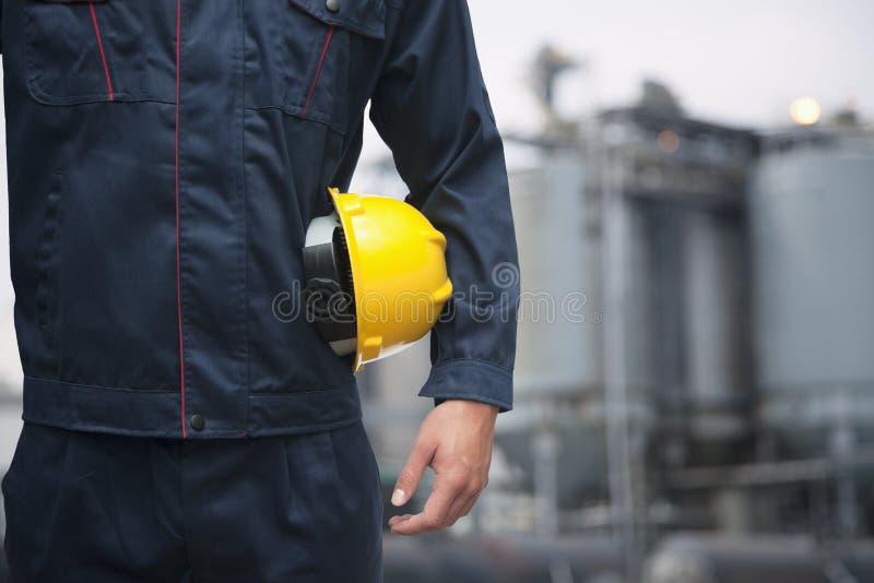 Seção mestra do trabalhador novo que guarda um capacete de segurança amarelo fora com a fábrica no fundo imagem de stock royalty free