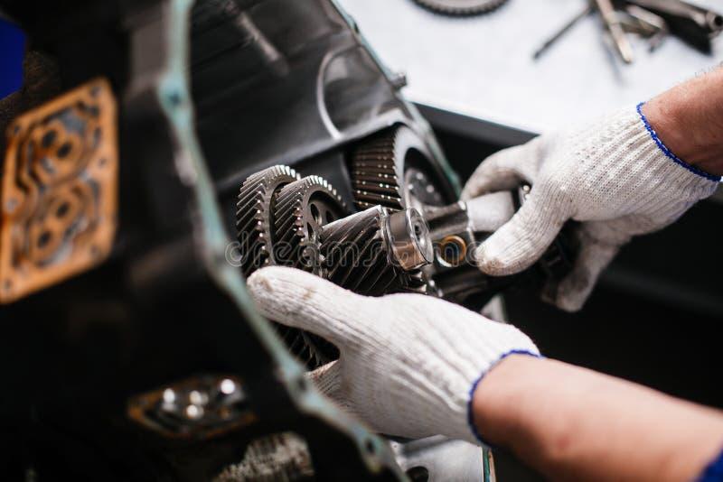 Seção transversal de uma caixa de engrenagens do carro trabalho dos mecânicos na garagem foto de stock