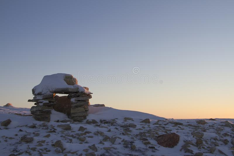 Señal de Inuksuk cubierta en nieve en la salida del sol encontrada en una colina cerca de la comunidad de bahía de Cambridge imagen de archivo libre de regalías