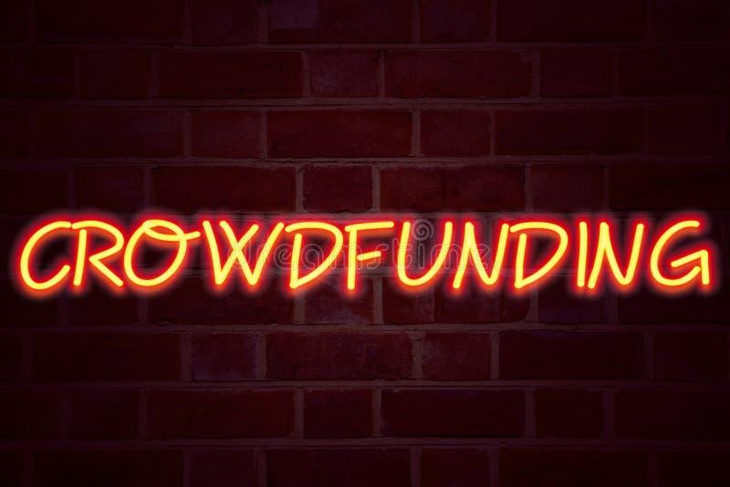 Señal de neón de Crowdfunding en fondo de la pared de ladrillo Muestra fluorescente del tubo de neón en el concepto del negocio d fotos de archivo