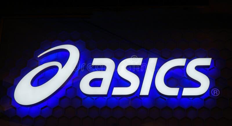 Señal de neón del azul del logotipo de Asics Asics es una compañía multinacional japonesa que produce calzado y el equipo de depo fotos de archivo libres de regalías
