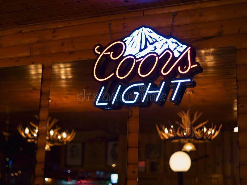 Señal de neón de la cerveza de Coors Light con la cabina de madera canadiense rústica en el fondo fotos de archivo libres de regalías
