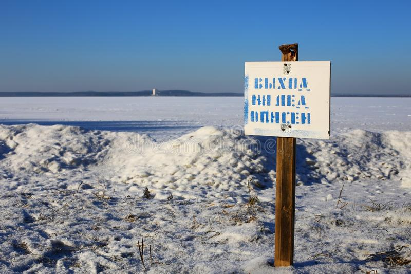 Señal de peligro del HIELO FINO en la orilla del lago fotos de archivo