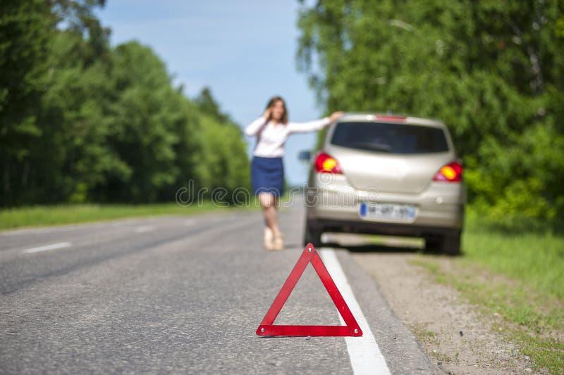 Señal de peligro del triángulo en el camino y la mujer con su coche después de b foto de archivo libre de regalías