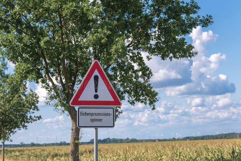 Señal de peligro en el borde de la carretera con la polilla procesional del roble de la inscripción fotos de archivo libres de regalías