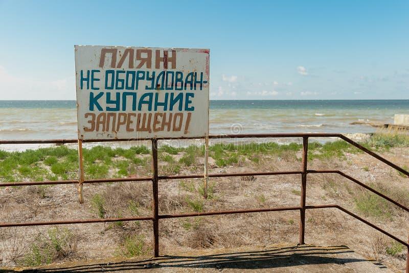 Señal de peligro en la orilla Texto en ruso: la playa no se equipa Se prohíbe la natación foto de archivo