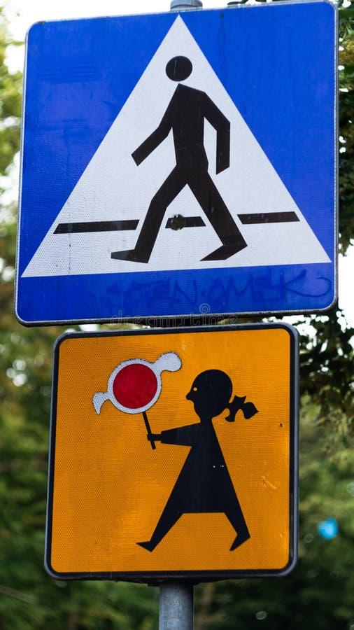 Señal de peligro de la escuela con el fondo de los árboles Muestra del paso de peatones con una muchacha imagenes de archivo