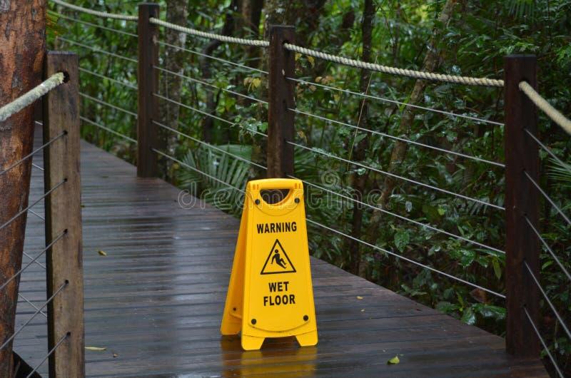Señal de peligro para el piso resbaladizo en una trayectoria de madera de las delanteras de una lluvia imagenes de archivo