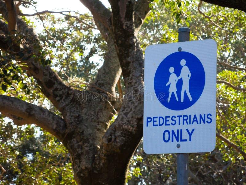Señal de peligro para los peatones solamente en la calzada en un parque público fotos de archivo libres de regalías