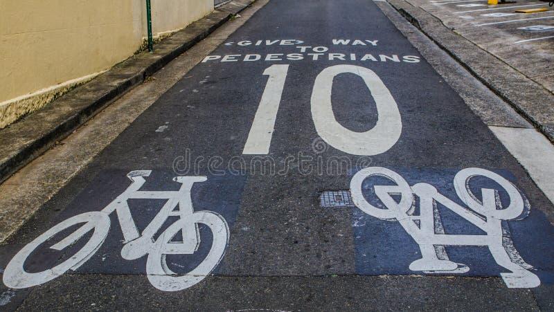 Señal de peligro para que un ciclista lleve a los peatones y al límite de velocidad, no sobre 10 kilómetros por hora, muestra pin imagen de archivo