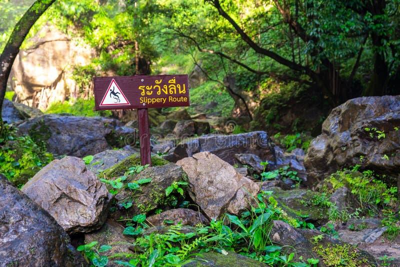 Señal de peligro resbaladiza de la ruta en la cascada del parque nacional imágenes de archivo libres de regalías