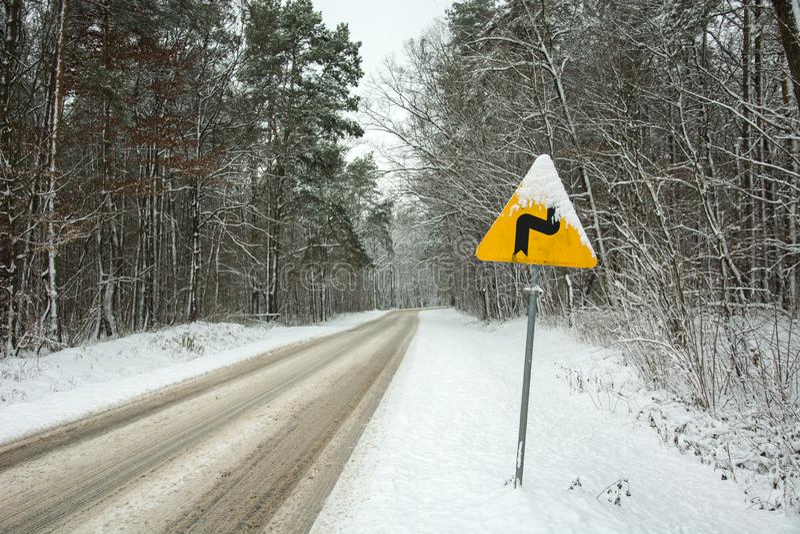 Señal de tráfico amonestadora amarilla - curvas peligrosas, primero correctas - haciendo una pausa el camino nevoso a través del  imágenes de archivo libres de regalías