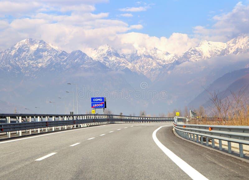 Señal de tráfico con la indicación de ir lago Como en Italia Tráfico en hihgway en las montañas italianas imagenes de archivo