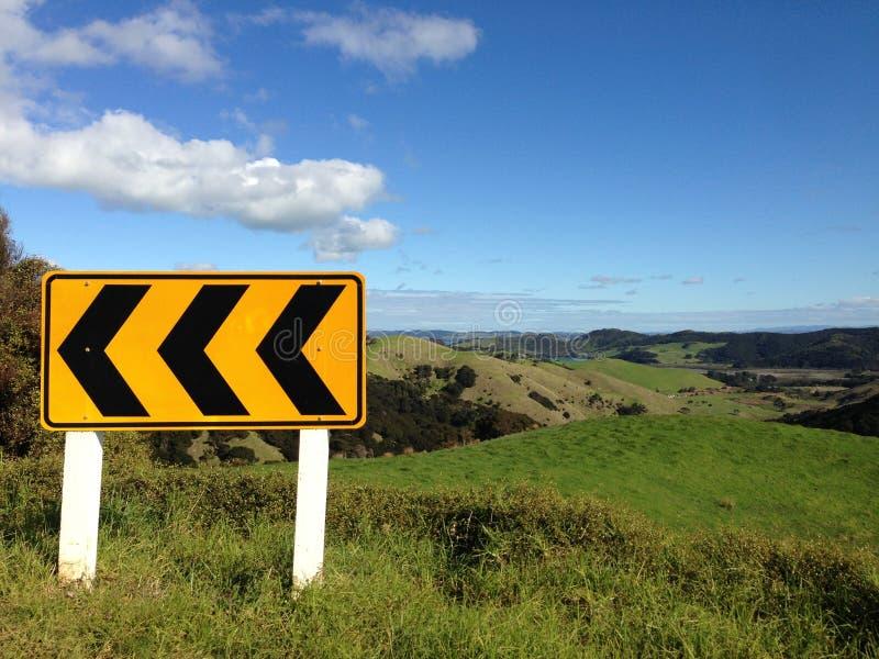 Señal de tráfico de la curva aguda en Nueva Zelanda rural imagen de archivo