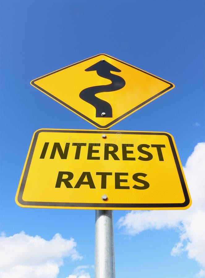 Señal de tráfico de levantamiento amarilla y negra de los tipos de interés en un cielo azul fotos de archivo libres de regalías