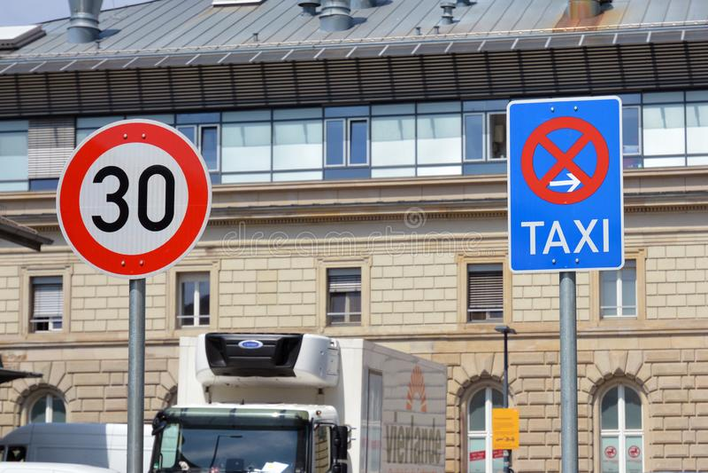 señal de tráfico del límite de velocidad 30kmh y extremo de la señal de tráfico que parquea de la fila de taxi al lado de cada un imagenes de archivo