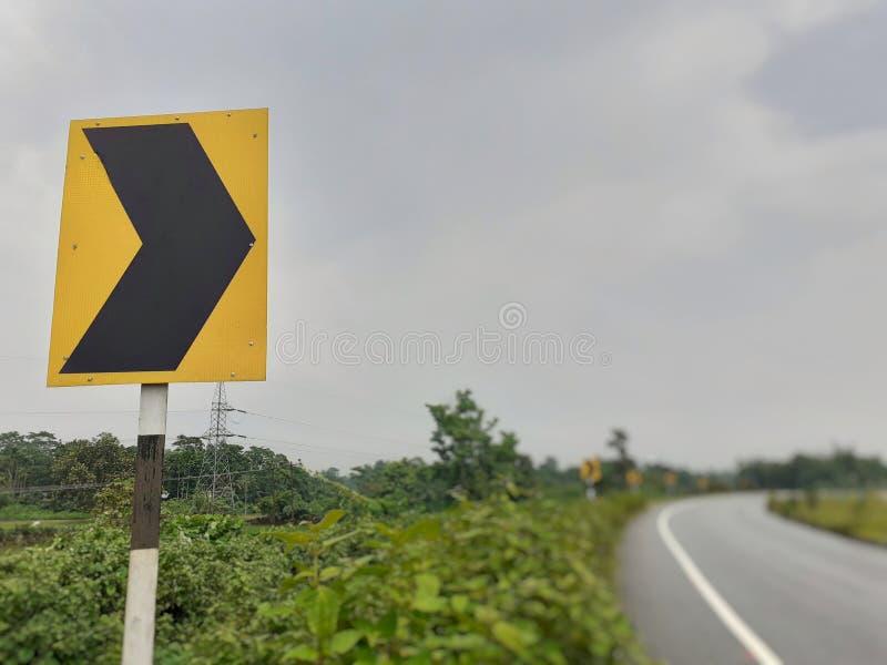 Señal de tráfico del tráfico del lado derecho de la curva en la carretera fotos de archivo