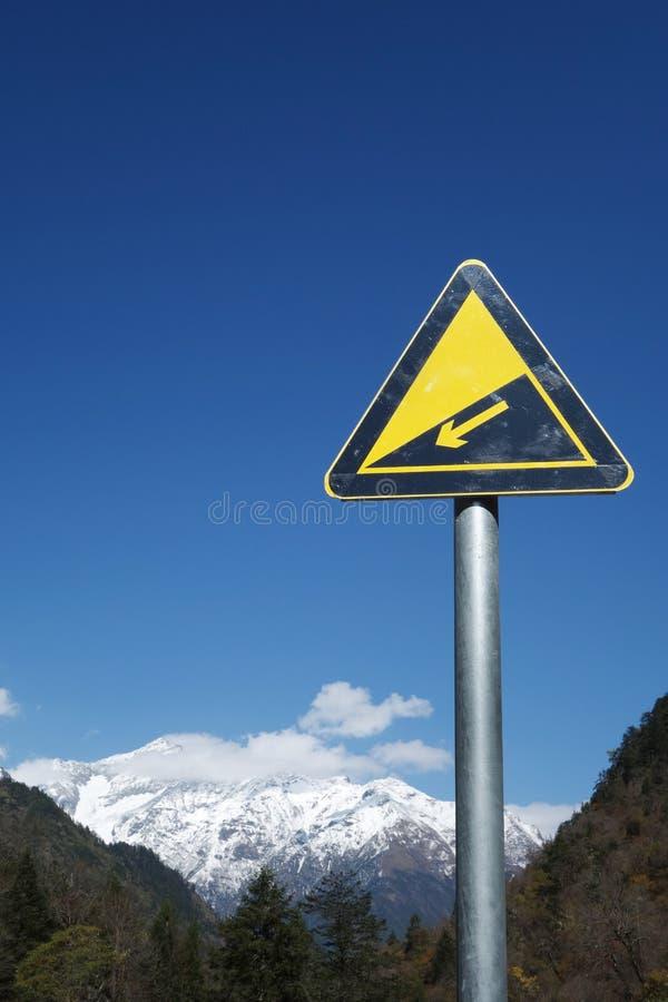 Señal de tráfico en declive con las montañas de la nieve imagen de archivo