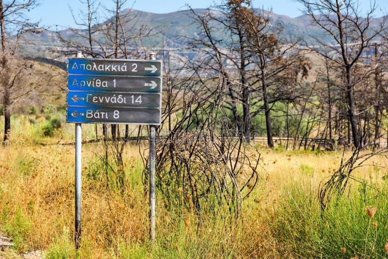 Señal de tráfico a los pueblos: Apolakkia, Arnitha, Genandi, Vati, quemado después del bushfire Rodas, Grecia foto de archivo libre de regalías