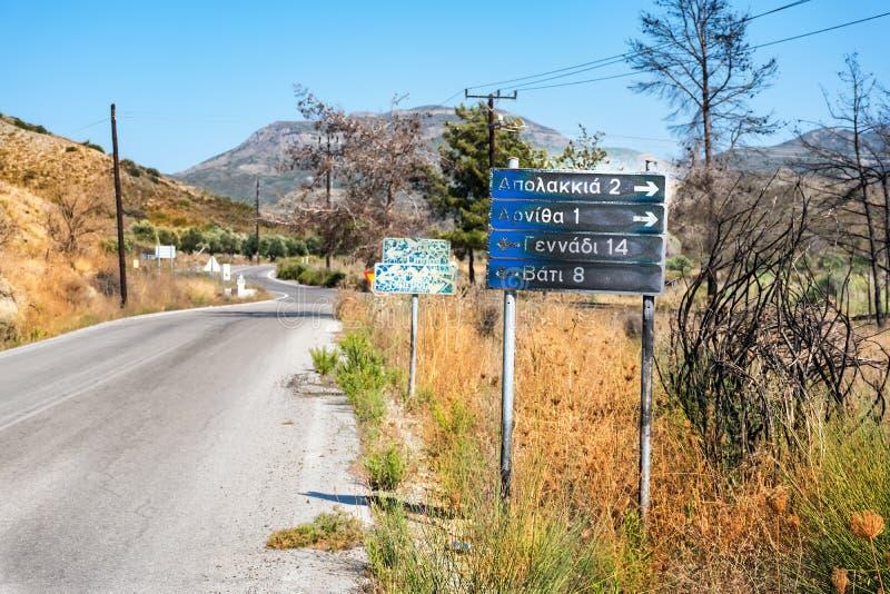 Señal de tráfico a los pueblos: Apolakkia, Arnitha, Genandi, Vati, quemado después del bushfire Rodas, Grecia fotografía de archivo libre de regalías