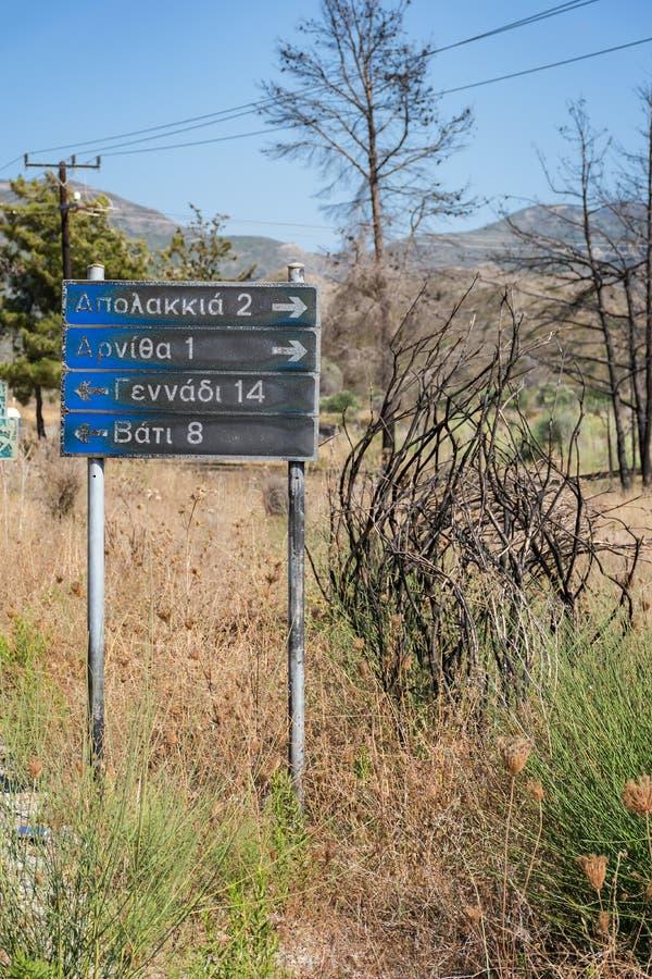 Señal de tráfico a los pueblos: Apolakkia, Arnitha, Genandi, Vati, quemado después del bushfire Rodas, Grecia fotos de archivo