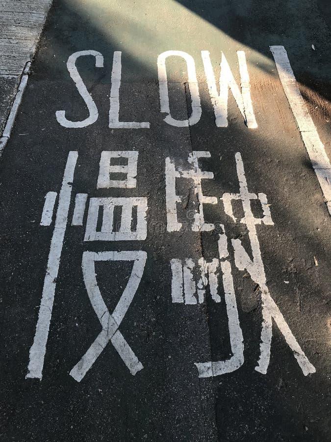 Señal de tráfico de marcado lento en un carril de bicicleta fotos de archivo