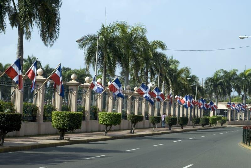 Señala el palacio del nacional por medio de una bandera de la República Dominicana imagen de archivo
